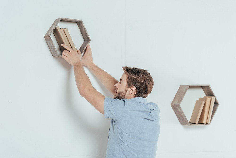 image of a man hanging trending octaganol shelving with a stud finder