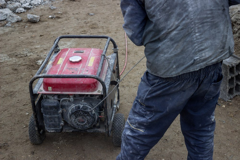 image of man starting dirty generator on building site