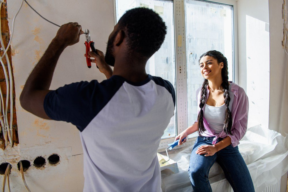 young couple remodeling wires in wall of home after cutting to expose studs and wires