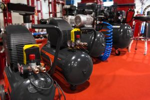 image of black air compressors for sale against red floor