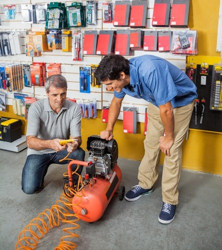 image of two men looking at a horizontal air compressor at a hardware store
