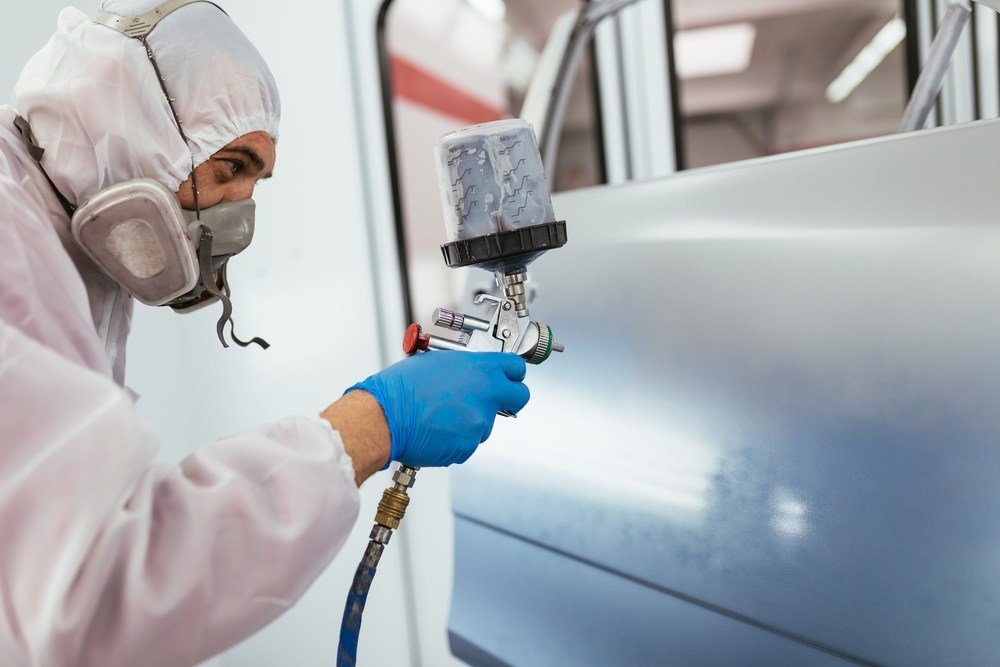 image of mechanic painting car with sprayer