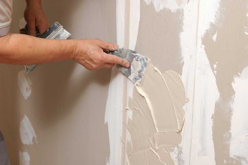 image of man adding joint compound to a wall