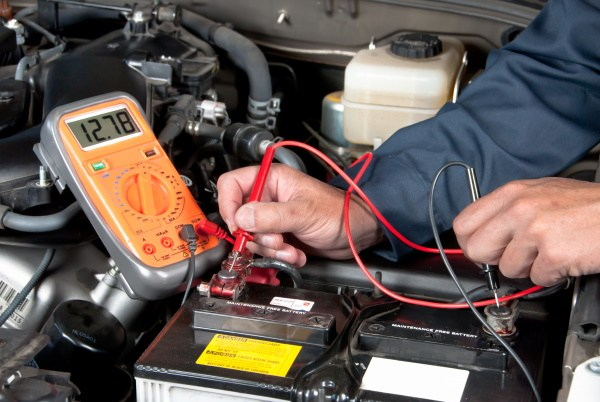 mechanic testing a battery and voltmeter reads 12.78